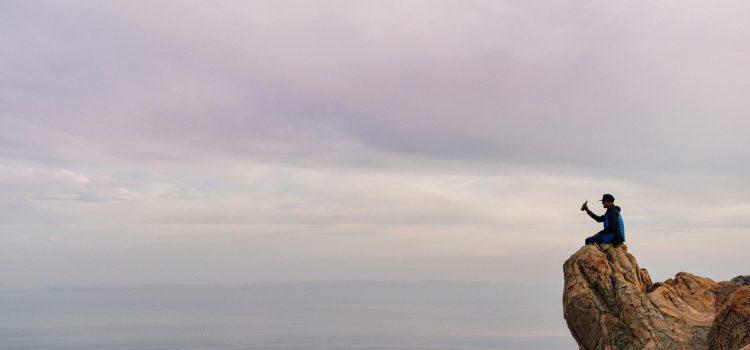 Un homme, du haut d'une falaise, s'apprête à jeter une bouteille à la mer dans l'espoir d'être compris